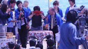 A man drinks sake from a ramen bowl at Dorome Matsuri, Japan