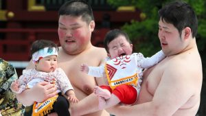 Two sumos with babies trying to make them cry