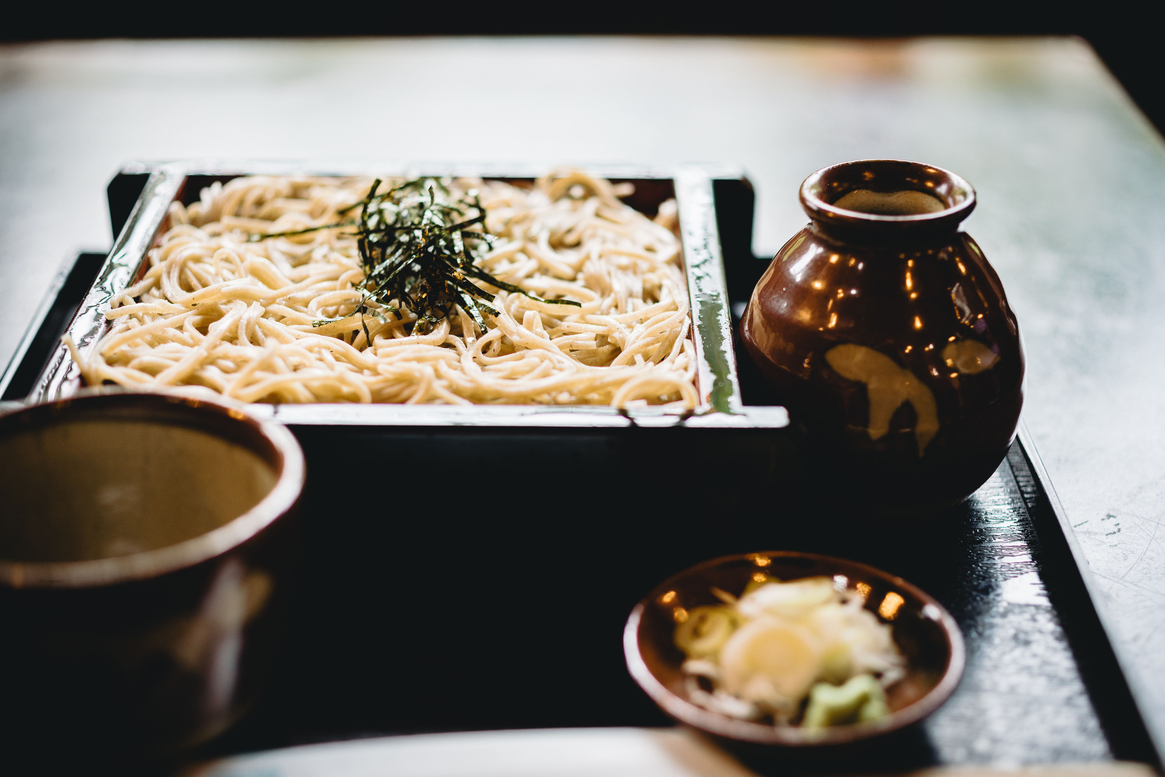 Soba noodles in a rectangle dish with a bottle of sake