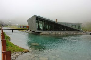 A modern building in the middle of a lake with surrounding mountains and fog