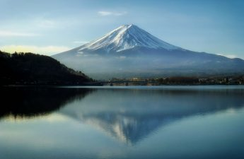 A view of Mount Fuji covered in snow reflecting on a lake, Japan.