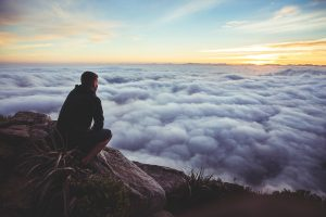 A man sits on a rock staring out at rolling clouds pondering something