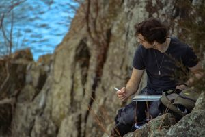 A man perched on a mountain is drawing something in the distance with a pen and paper