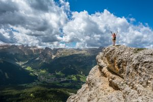A backpacking woman with her hands in the air stands on the edge of a cliff