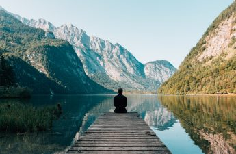 Man sitting on the edge of a pier looking out onto a lake with mountains