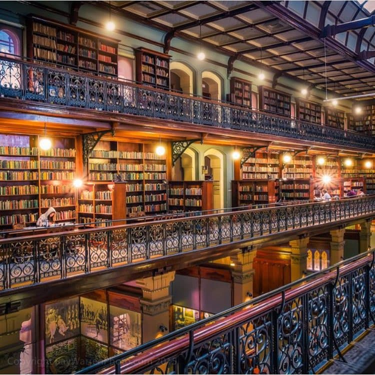 old library with wooden and metal beams and many books