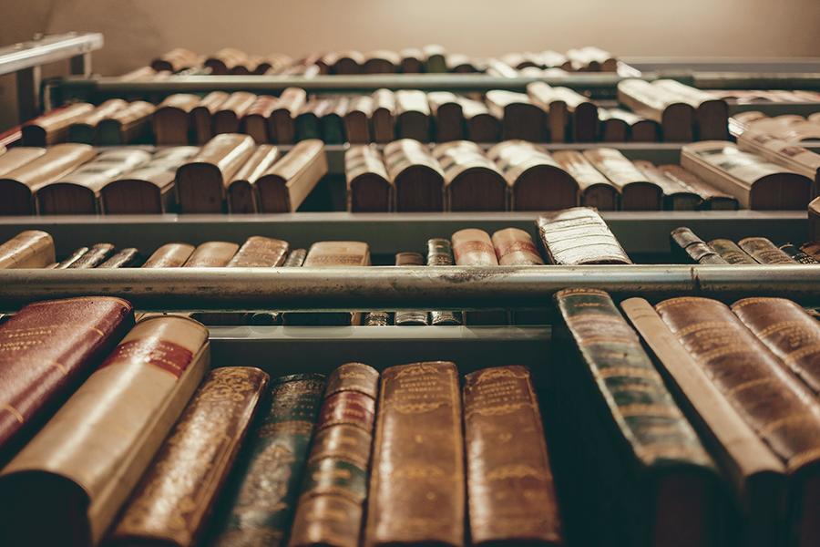 Upwards shot of old books stacked on shelves