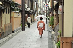 A woman in kimono walks along a street in Kyoto