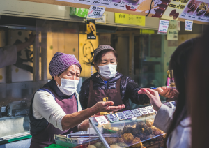 Two women serving food in masks in japan