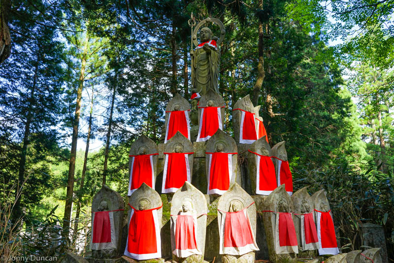 Spiritual Japanese statues with red aprons sit in a forest