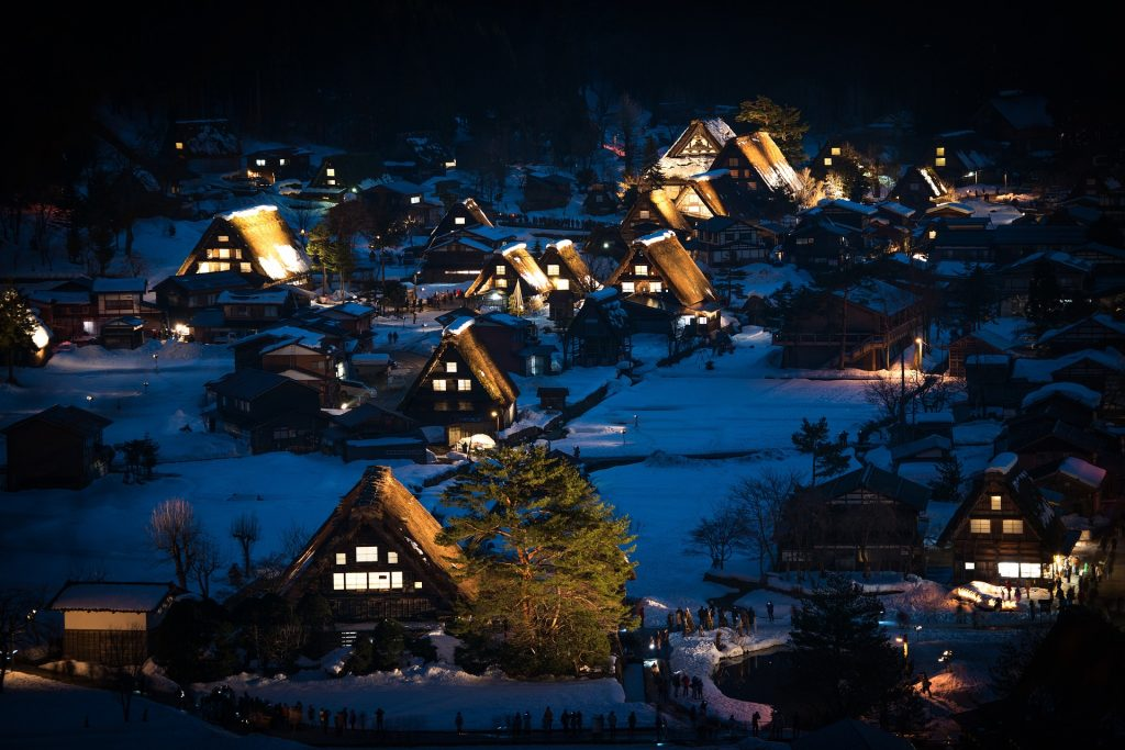 Snowy village with lights on in thatched houses