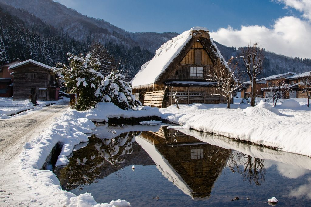 A thatched house covered in snow